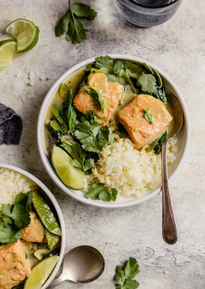 white bowl filled with cauliflower rice, large chunks of salmon and green curry sauce
