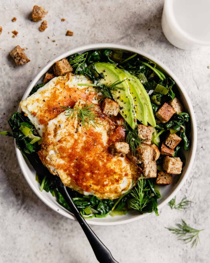 white bowl filled with greens, eggs, avocado and croutons