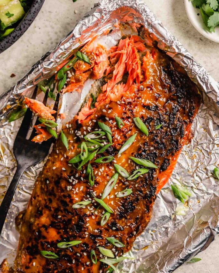 glazed salmon fillet on a foil-lined baking sheet topped with green onions and sesame seeds