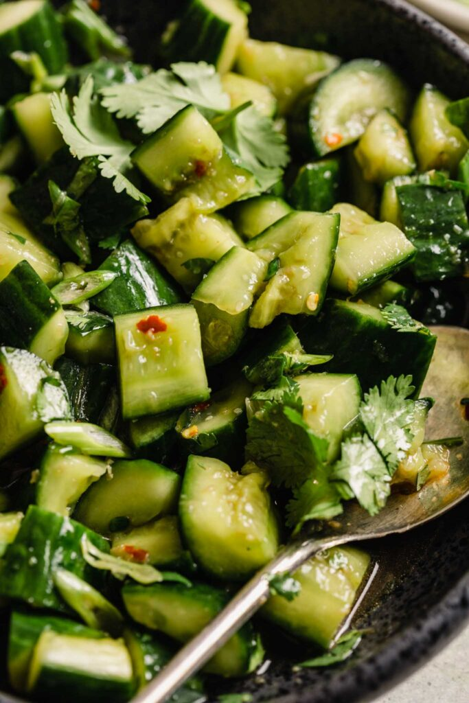 close up of crushed cucumber chunks with red pepper flakes and dressing