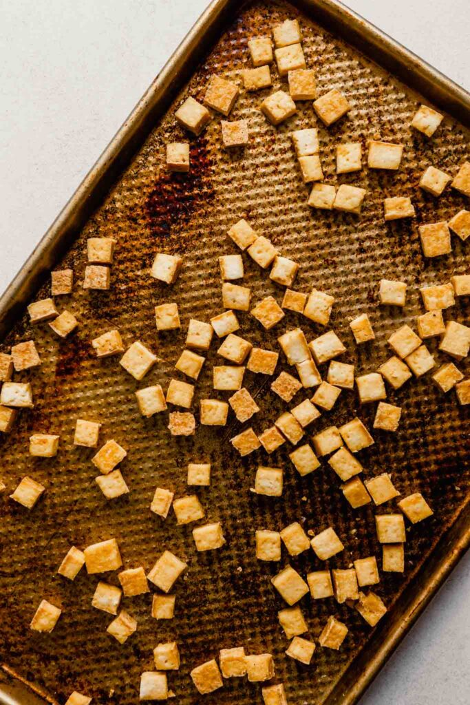 cooked cubes of tofu on a baking sheet