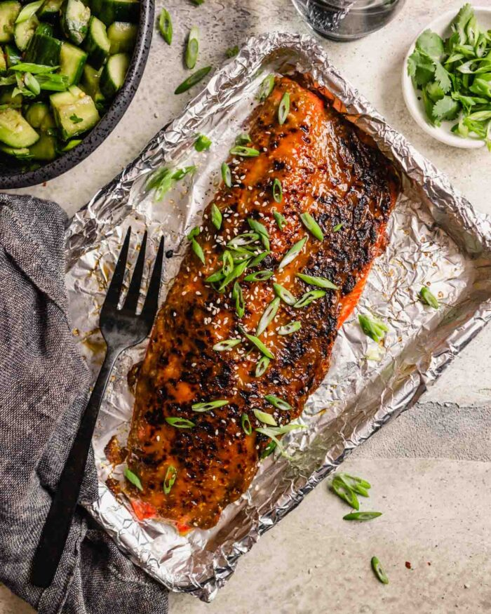 roasted glazed salmon fillet on a foil-lined baking sheet with sliced green onions and sesame seeds sprinkled over top