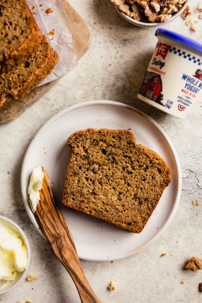 slice of banana bread set on a white plate with a wooden knife with butter on it