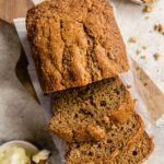 banana bread, partially sliced, set on a piece of white parchment paper set on wood cutting board