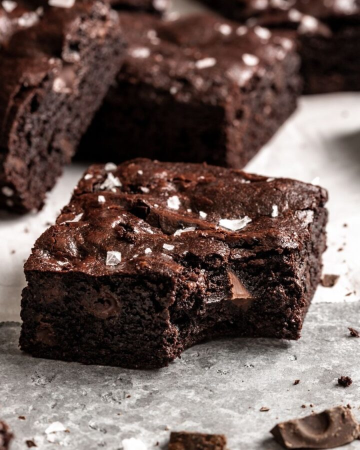 a square brownie with a bite taken out of it, with brownies stacked in the background