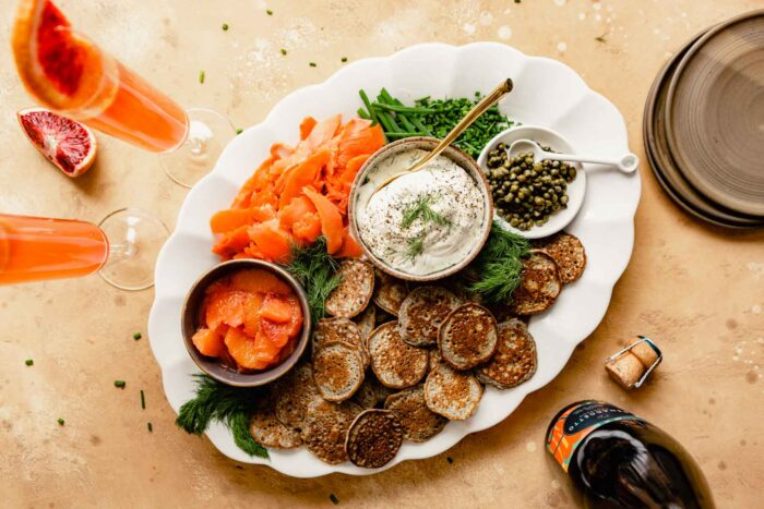 small buckwheat pancakes topped with cream cheese, salmon, capers and dill on a brown plate