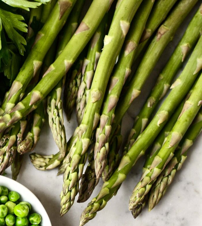 raw asparagus spears on a white table
