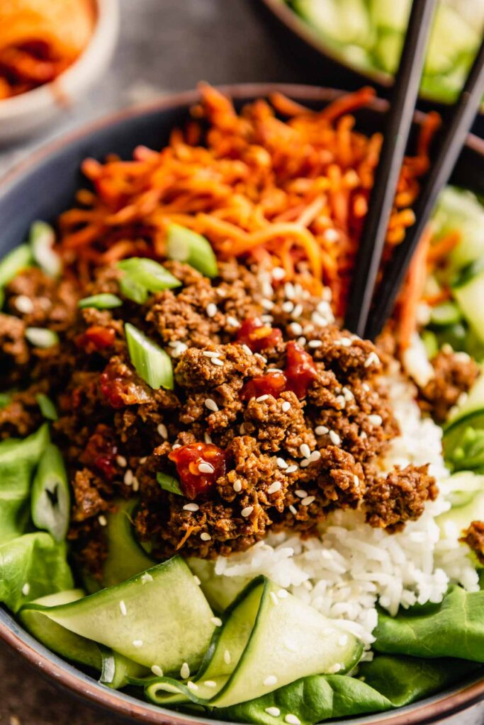 blue bowls filled with ground beef over rice, carrots and cucumbers