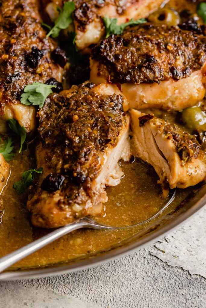 close up image of crusted chicken thighs in a skillet with sauce and olives