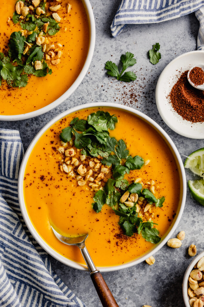 white bowl filled with an orange pureed soup topped with chopped peanut, cilantro and sumac