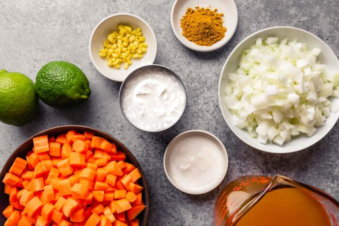 diced carrots, coconut milk, coconut oil, lime, minced ginger, curry powder, onions and borth measured out on a counter