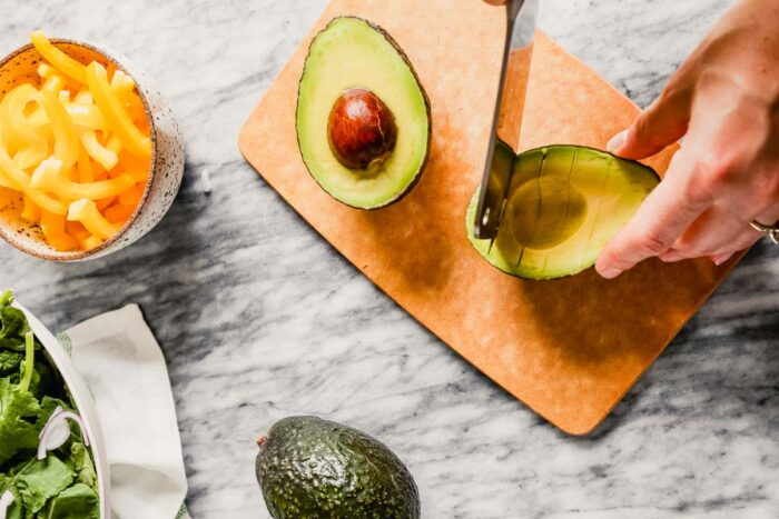 hands cutting an avocado on a small brown cutting board