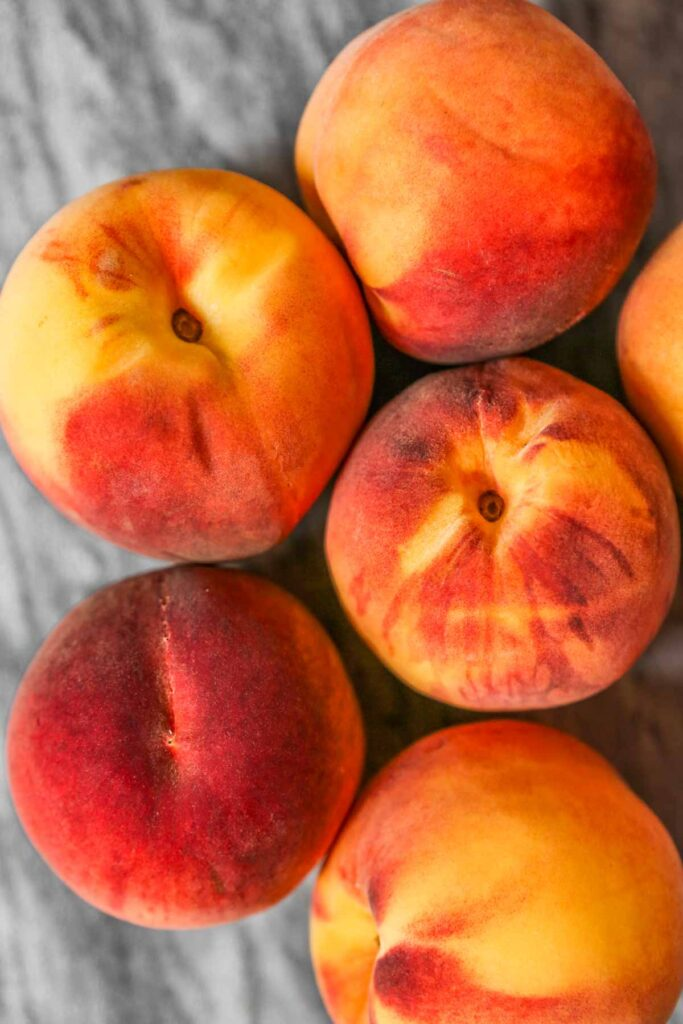 ripe peaches set on a gray marble counter