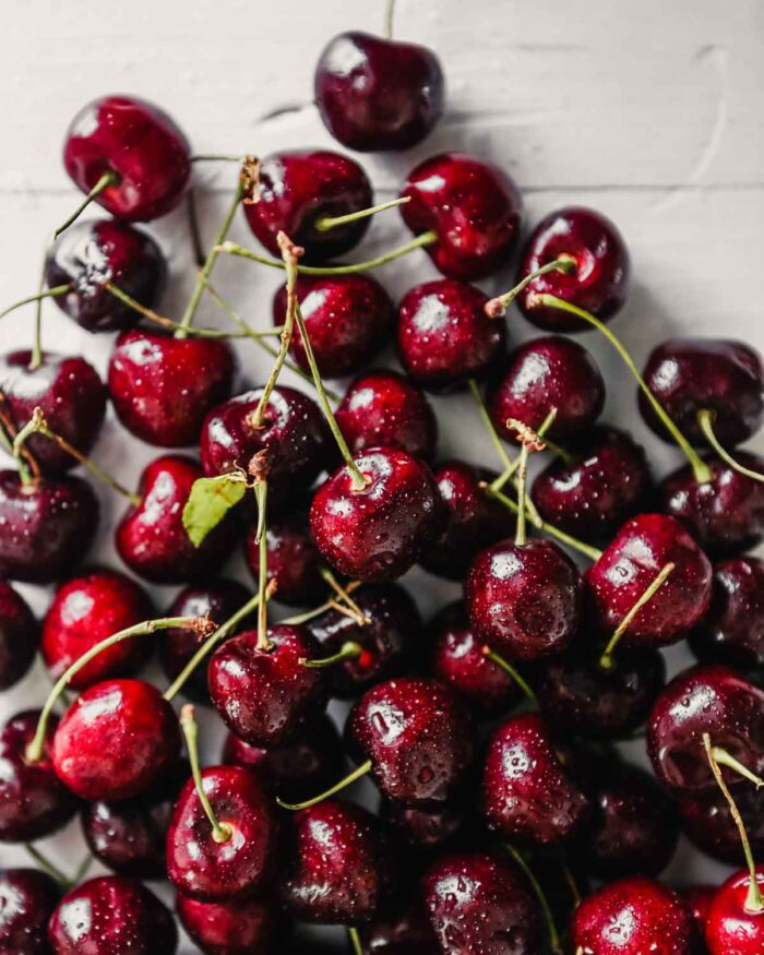 fresh cherries, with water droplets on them, set on a white wooden table