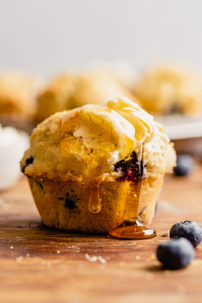 a blueberry muffin set on a brown table with honey dripping down it.