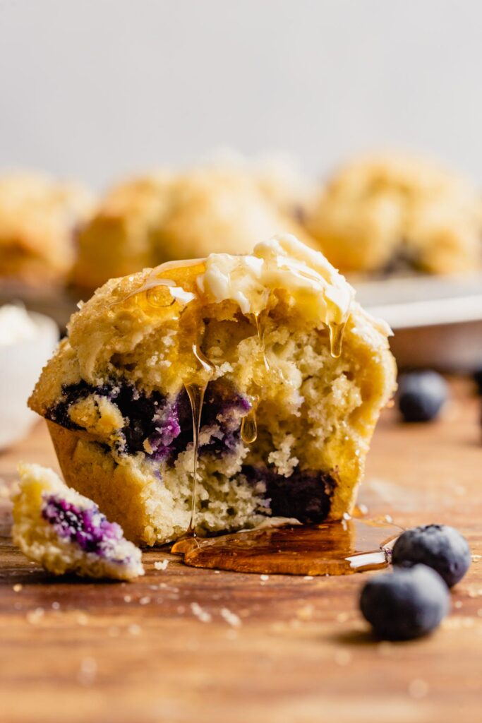A blueberry muffin set on a wood table with a bite taken out of it and honey dripping down it