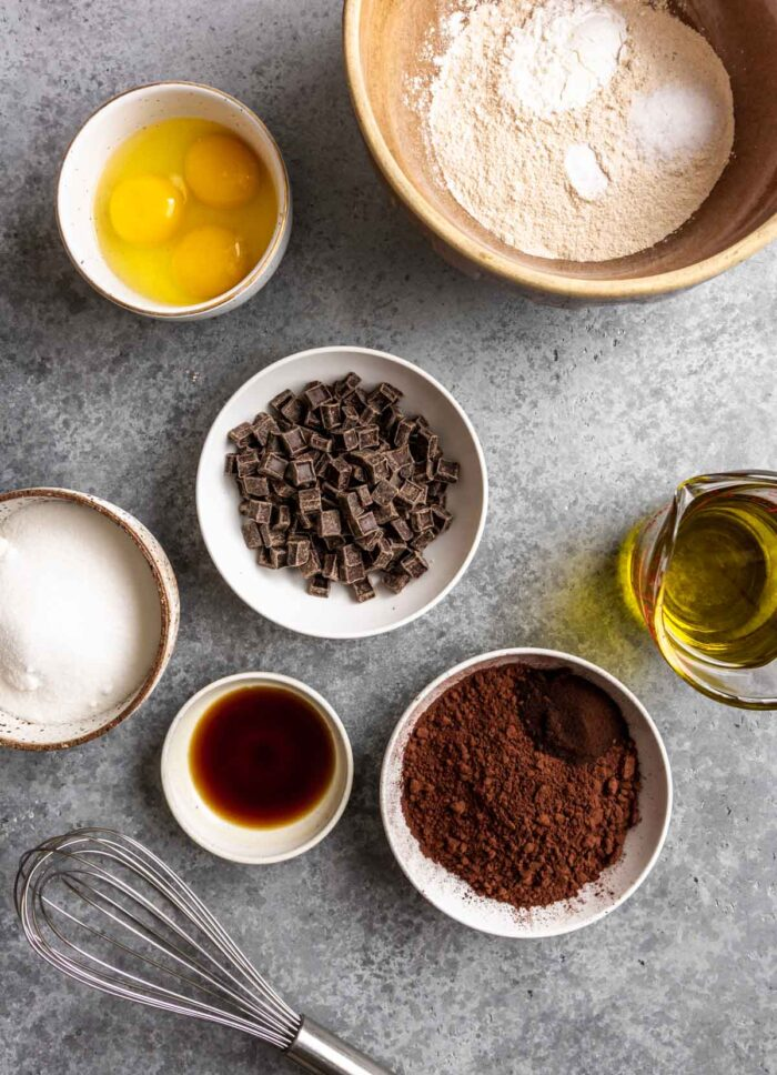 flour, cocoa powder, chocolate chips, olive oil, sugar, eggs, vanilla and a whisk set on a blue-gray counter