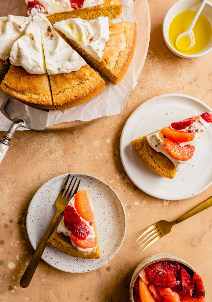 slices of cake topped with whipped cream and oranges on white plates with gold forks, whole round cake cut into pieces set on a wood board off to the top