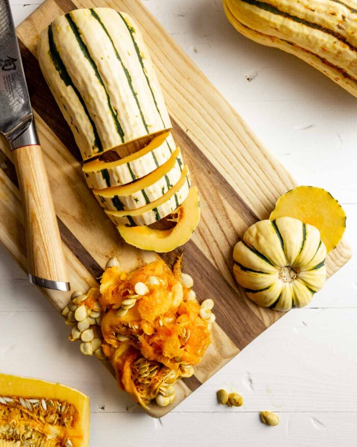 delicata squash halve on a cutting board, cut into slices