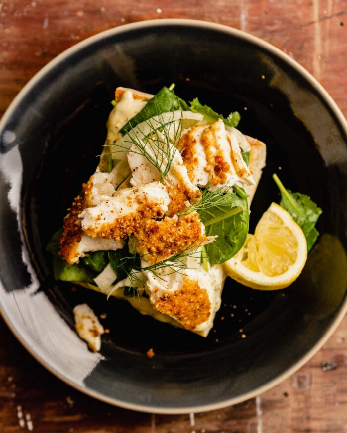 open-faced sandwich topped with fish and lettuce set on a blue plate on a brown wooden table