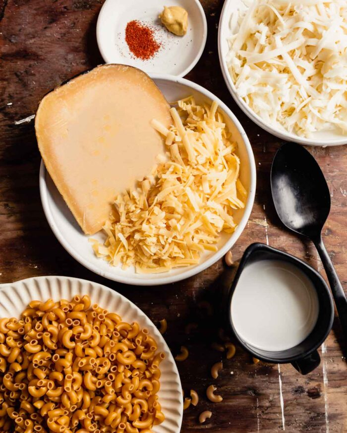 uncooked elbow noodles, shredded cheese, milk, and spices measured out in white bowls on a wood table