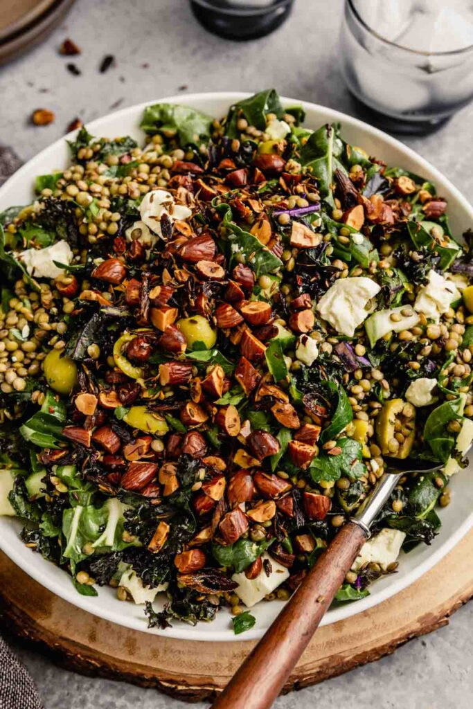kale and lentil salad in a white bowl set on a wood board topped with feta cheese and toasted almonds