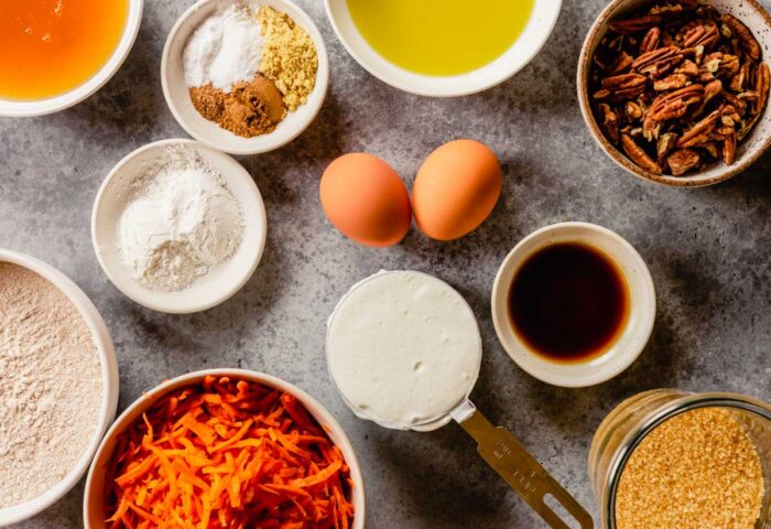 olive oil, honey, shredded carrots, flour, spices, yogurt, and vanilla measured out in bowls. Eggs arranged around bowl