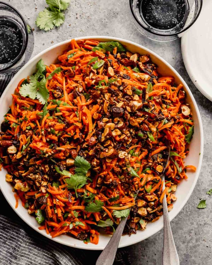 shredded carrot salad in a white bowl set on a gray table with glasses set around it