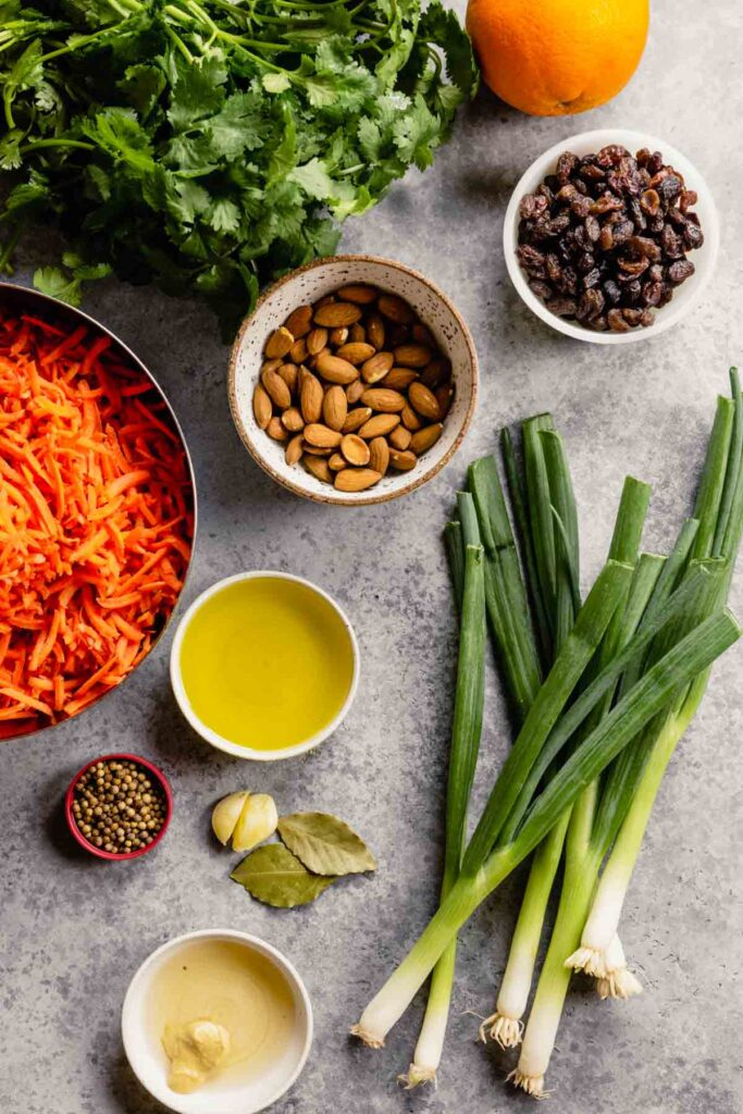 scallions, shredded carrots, raw almonds, bay leaves, garlic cloves, coriander seeds, raisins and cilantro measured and set out on a gray table