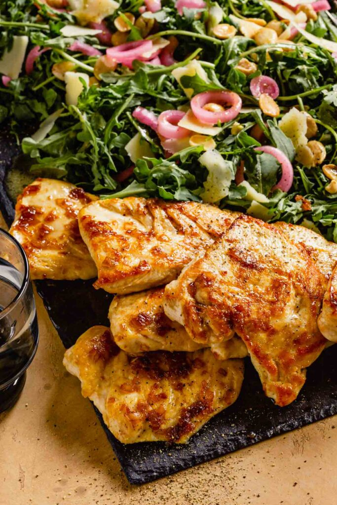 golden brown chicken on a slate board with arugula salad topped with pickled red onion, parmesan and almonds