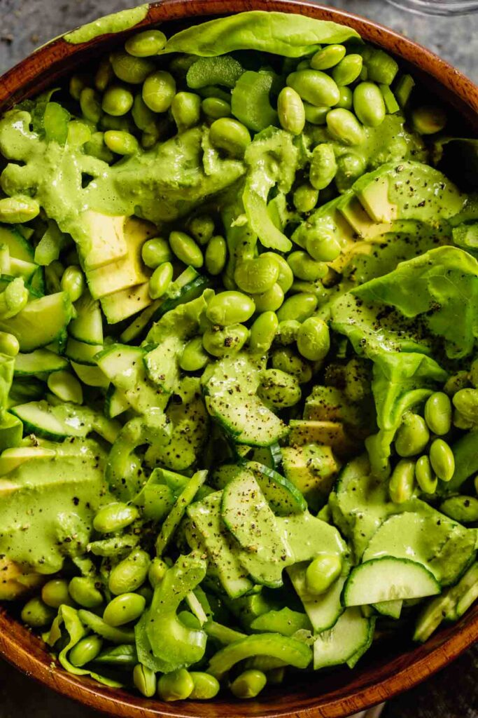 wood bowl filled with lettuce, vegetables and topped with a green goddess dressing