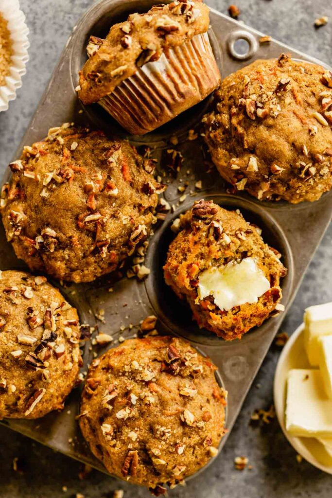 muffins in a muffin tin with pecans scattered around and butter set next to it