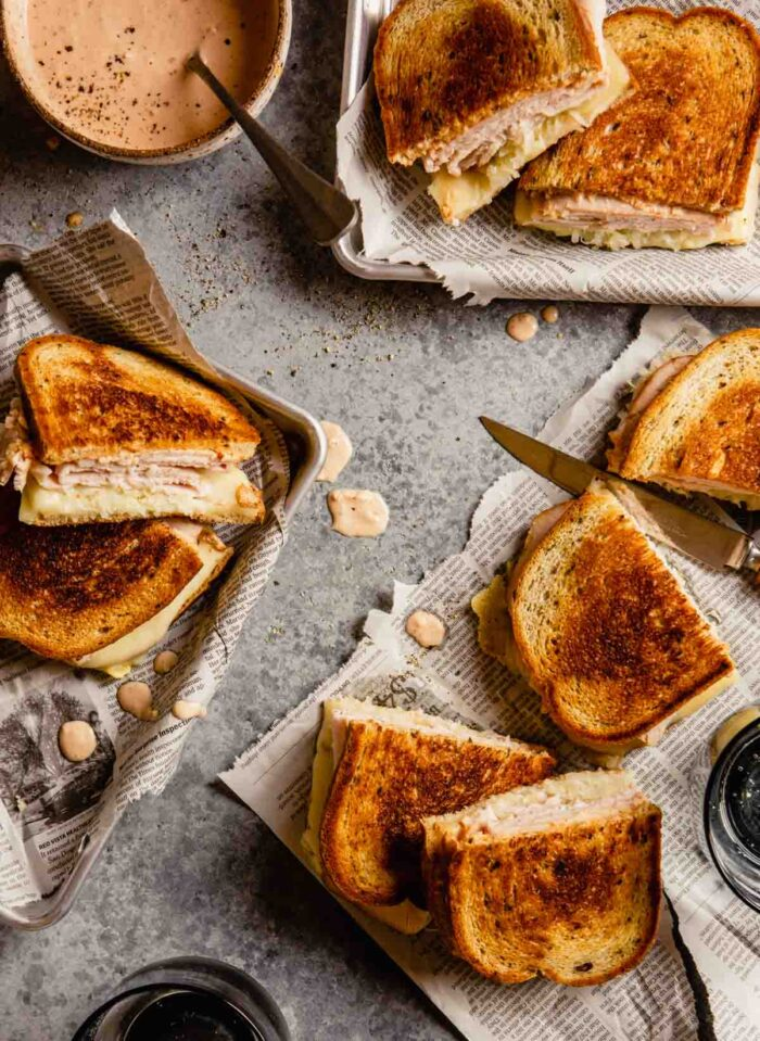 grilled sandwiches on newspaper set in metal trays with drips of sauce scattered around