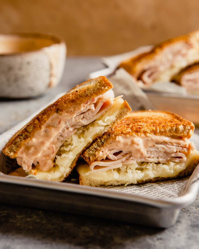 Reuben sandwich halves stacked on a parchment-lined baking sheet