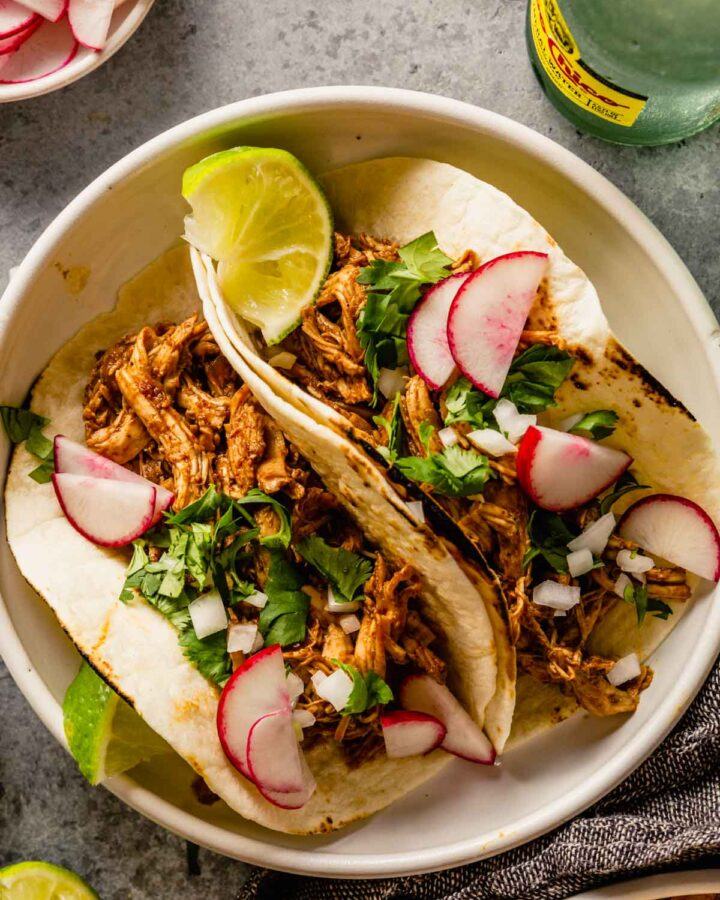 shredded chicken tacos in a white bowl topped with radish slices, lime wedges, white onion and cilantro.