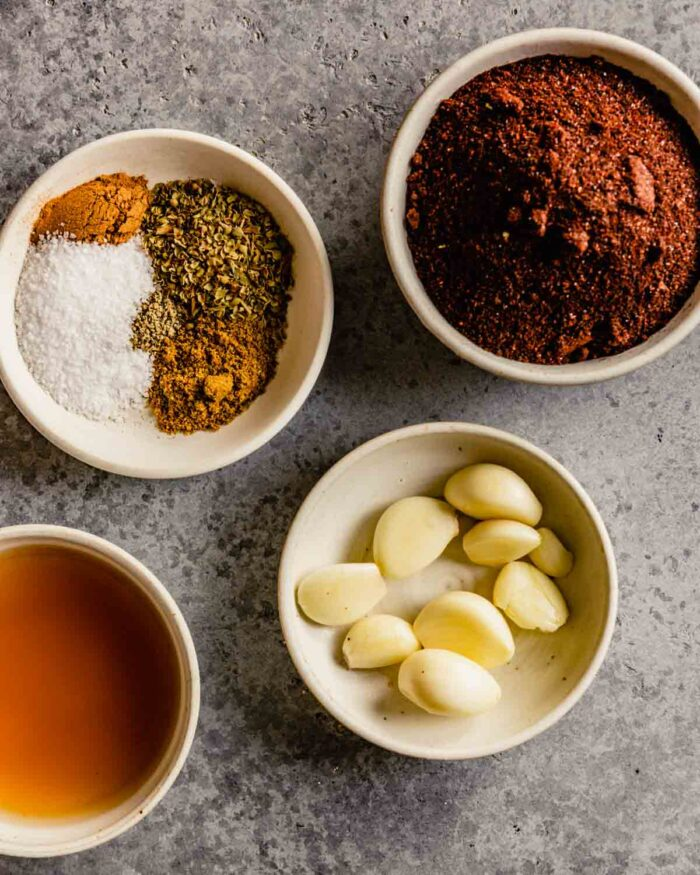spices, garlic and vinegar measured out in small white bowls