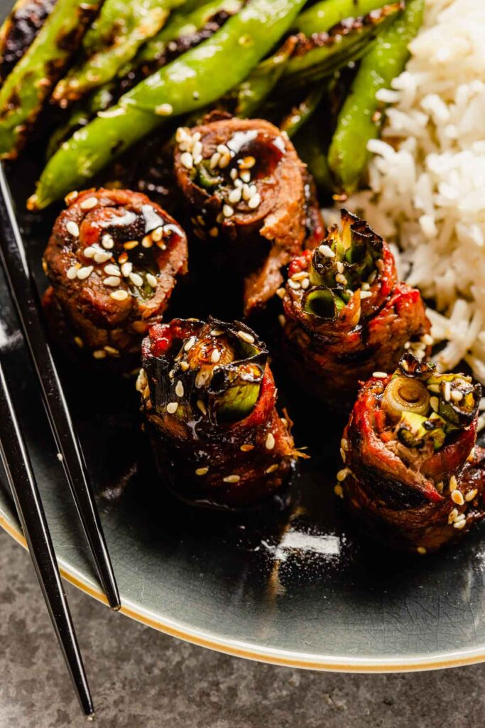 beef scallion rolls on a plate with charred snap peas and white rice