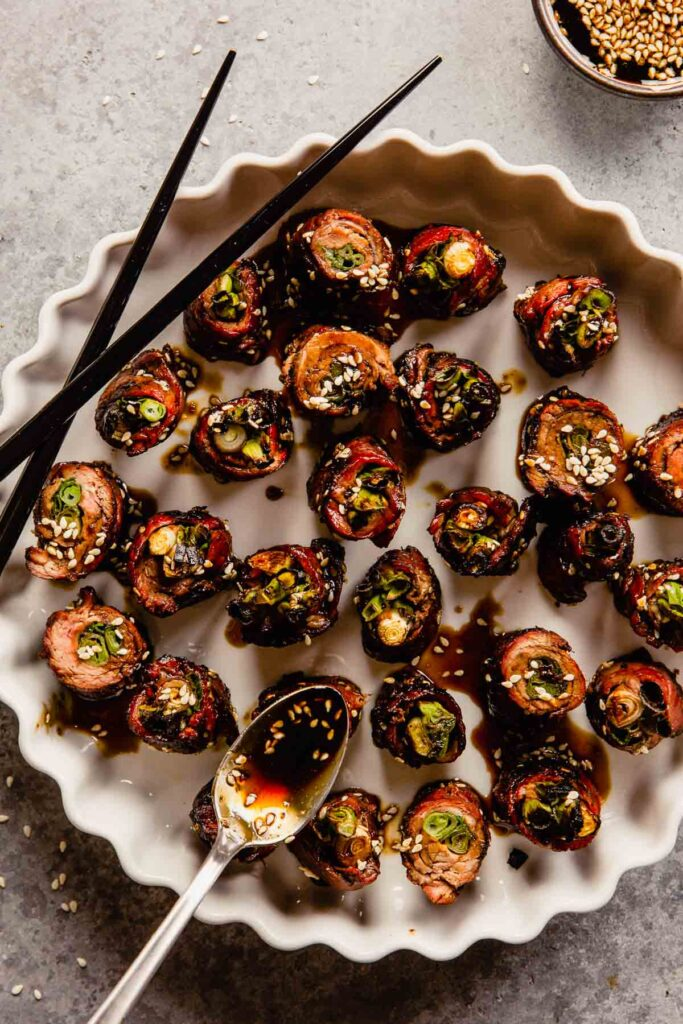 beef scallion rolls set on a large white platter with a glaze being spooned over top