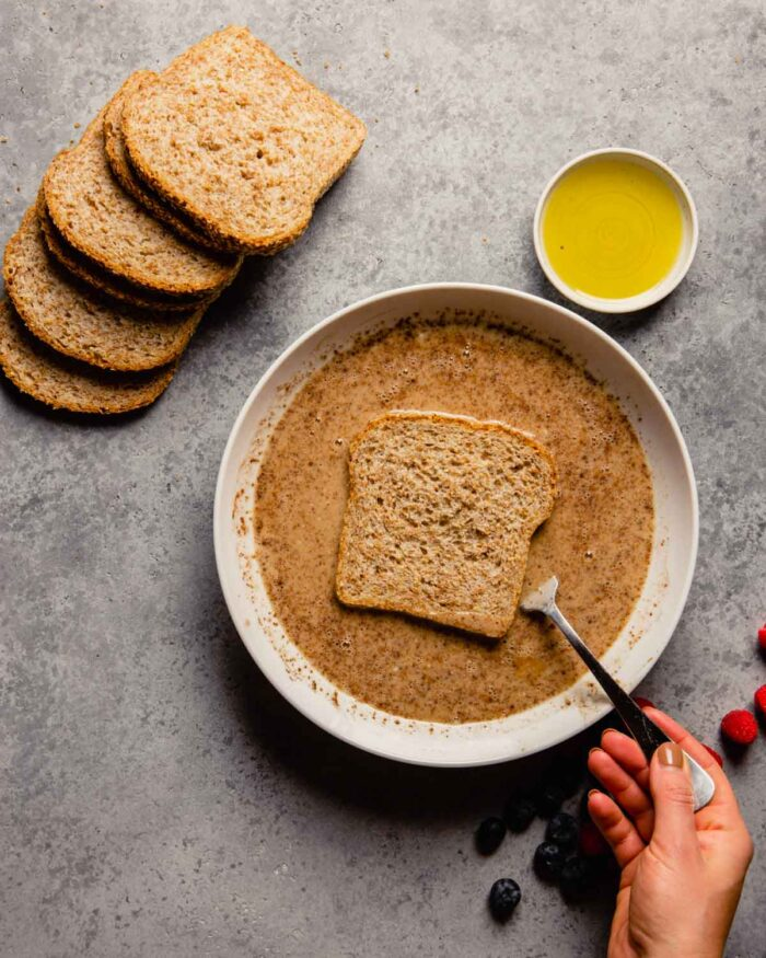 whole grain bread being soaked in a custard mixture
