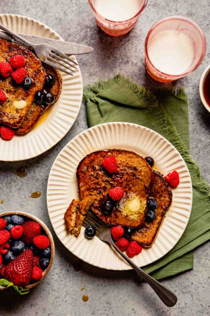 french toast topped with berries, butter and maple syrup on a white plate with a green napkin set next to it