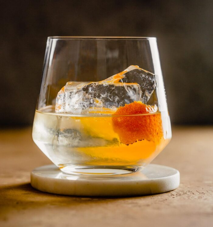rocks glass filled with a clear liquid, orange peel and large chunk of ice set on a white coaster.