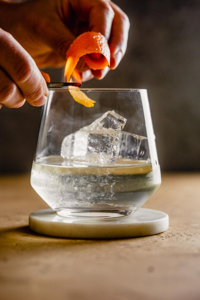 rocks glass filled with a clear liquid and large chunk of ice set on a white coaster. Someone flaming an orange peel over top