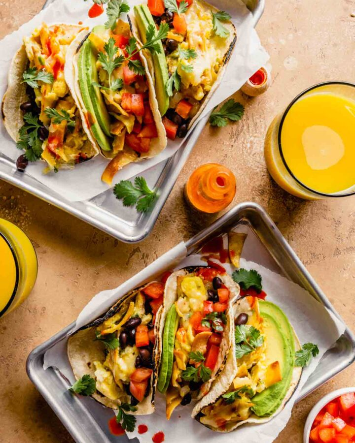 breakfast tacos filled with scrambled eggs, avocado slices, tomatoes, black beans on silver trays with parchment paper. Orange juice and hot sauce set around