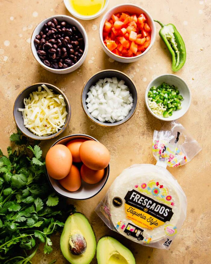 shredded cheese, diced onion, diced tomato, sliced green onions, jalapeno, cilantro, and eggs measured out and arranged on a light brown table