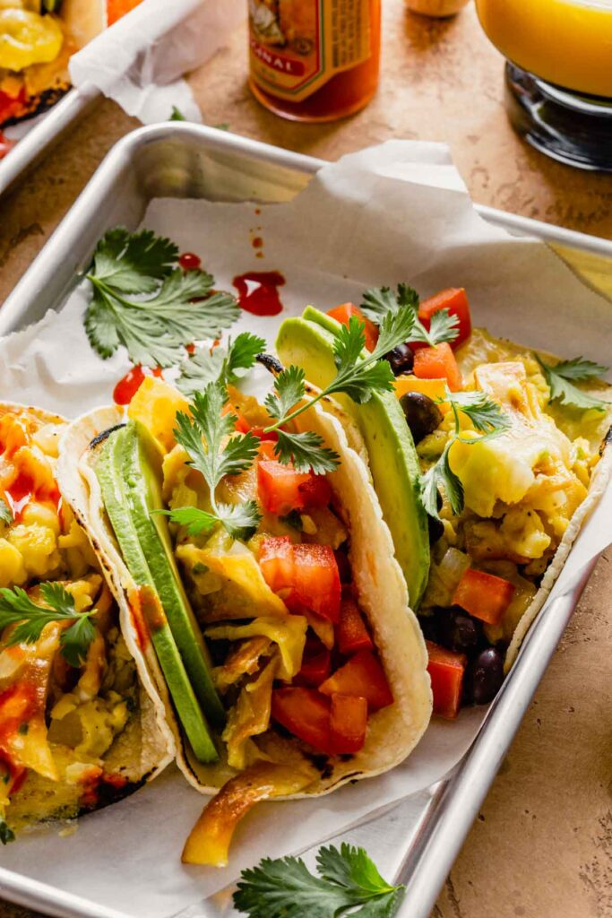 breakfast tacos filled with scrambled eggs, black beans, tomatoes, avocado slices and cilantro set on parchment paper-lined trays