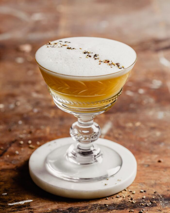 A yellow-colored dink in a coupe-style glass with a foam layer on top