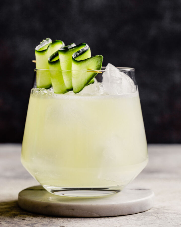 rocks glass filled with a light yellow-colored drink and topped with a cucumber ribbon