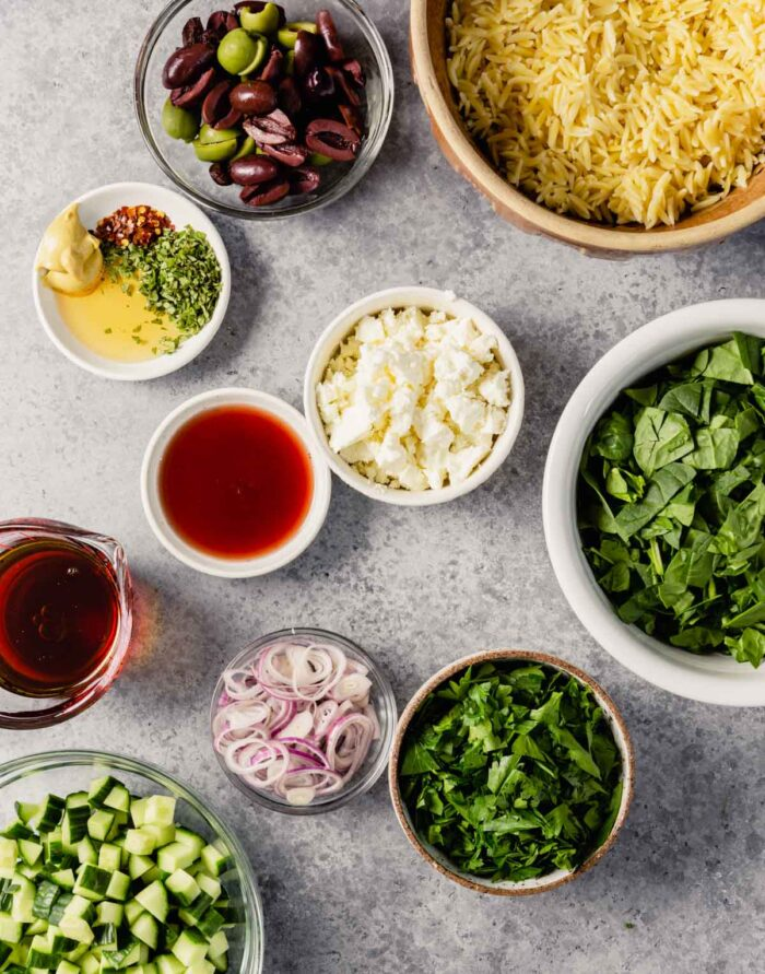 cooked orzo, vinegar, feta, olives, spinach, parsley, cucumbers, and shallots prepped and measured out in bowls on a gray table
