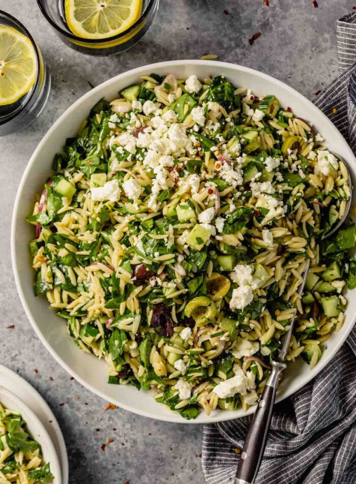 orzo pasta salad with spinach, olives and cucumbers in a large white bowl