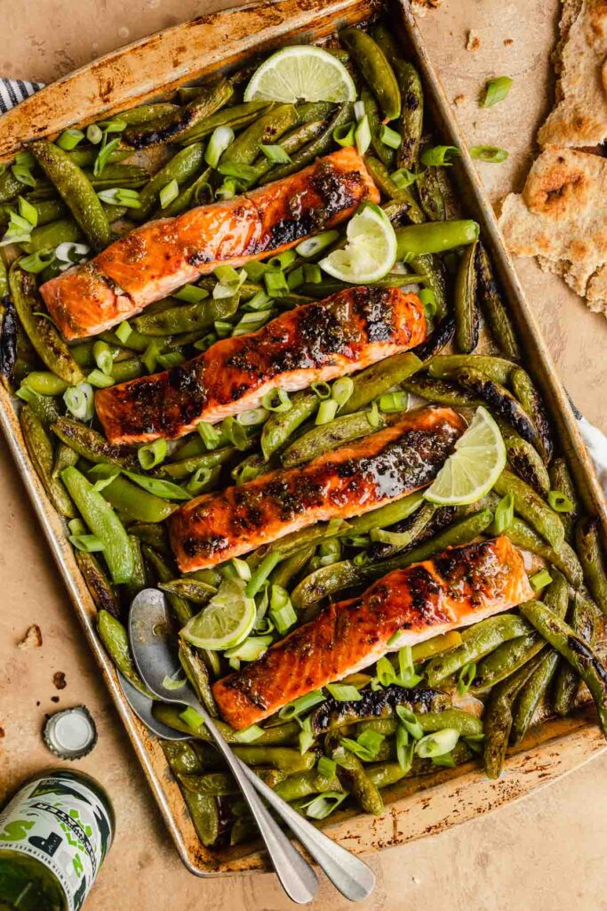 glazed salmon fillets on a baking sheet surrounded by snap peas.
